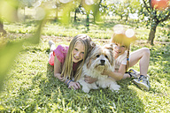 Two smiling sisters lying with dog on meadow - SHKF00761