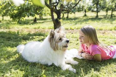 Girl lying with dog on meadow - SHKF00764