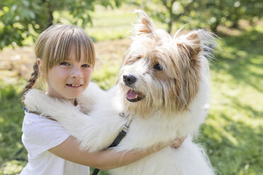 Girl playing with dog on meadow - SHKF00767