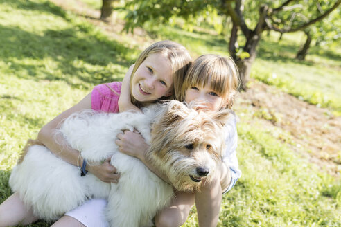 Two smiling sisters cuddling with dog on meadow - SHKF00770