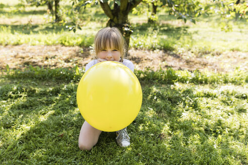 Girl inflating balloon on meadow - SHKF00773