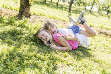 Two happy sisters playing in meadow - SHKF00776