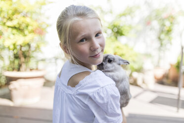 Portrait of girl with rabbit outdoors - SHKF00785