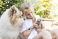 Girl with rabbit and dog outdoors - SHKF00788