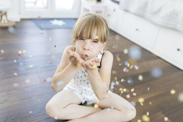 Girl at home sitting on floor blowing confetti - SHKF00791