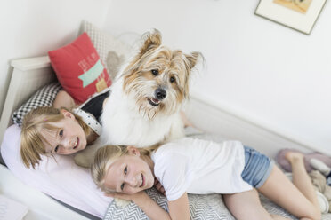 Two sisters cuddling with dog in bed - SHKF00794