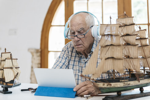 Senior man wearing headphones working on model ship on table with tablet - JRFF01407