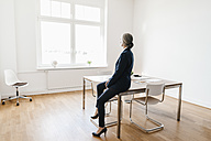 Businesswoman sitting on table in office looking out of window - KNSF01781