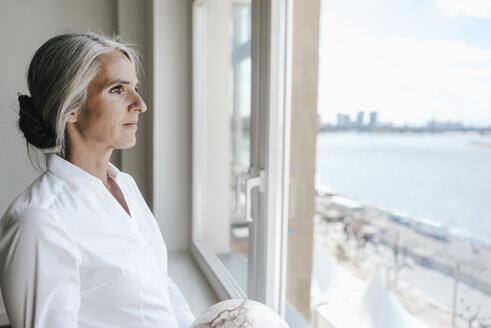 Businesswoman in office looking out of window - KNSF01784