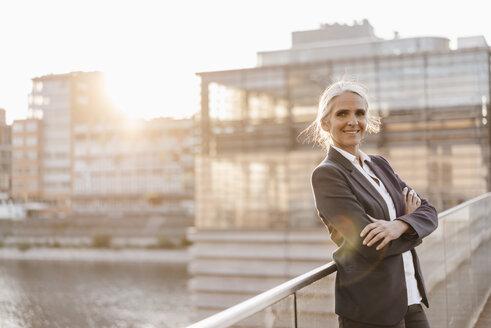Portrait of confident businesswoman standing on bridge - KNSF01787