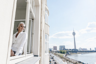 Businesswoman looking out of window in waterfront office - KNSF01790