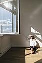 Businesswoman sitting on floor in office - KNSF01793