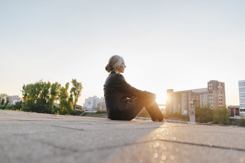 Businesswoman sitting outdoors at sunset - KNSF01799