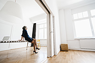 Businesswoman sitting on table in modern office - KNSF01808
