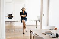 Businesswoman sitting on table in modern office - KNSF01820