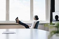 Businesswoman in office sitting at the window looking out - KNSF01823