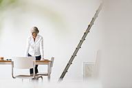 Businesswoman standing in modern office - KNSF01826
