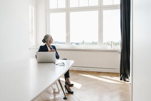 Businesswoman working on laptop in office - KNSF01838