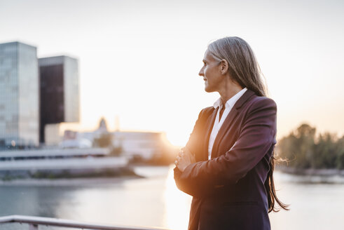 Confident businesswoman outdoors at sunset - KNSF01844