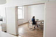 Businesswoman working on laptop in office - KNSF01853