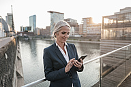 Smiling businesswoman using cell phone on bridge - KNSF01856
