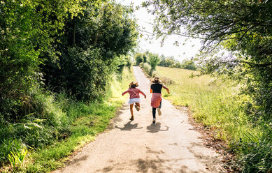 Two little girls running down a lane outdoors - MGOF03427