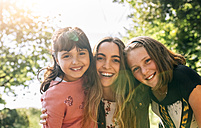 Portrait of three happy girls outdoors - MGOF03430