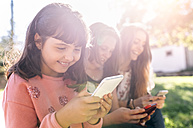 Three happy girls using their smartphones outdoors - MGOF03436