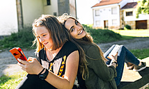 Two happy girls using their smartphones outdoors - MGOF03442