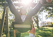 Happy young woman on a swing - MGOF03445