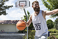 Laughing man playing basketball on outdoor court - MAEF12345