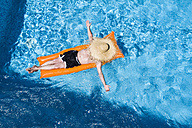 Man relaxing on orange airbed in swimming pool - MAEF12348