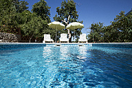 Croatia, Istria, three empty sun loungers at swimming pool - MAEF12351