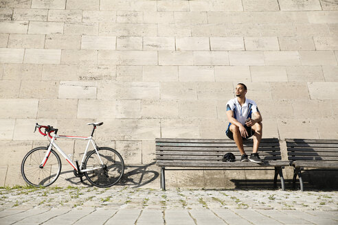 Young man with racing bicycle having a break - FKF02426