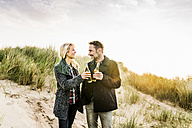 Happy couple in dunes clinking beer bottles - FMKF04202