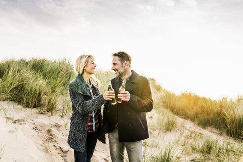 Happy couple in dunes clinking beer bottles - FMKF04202