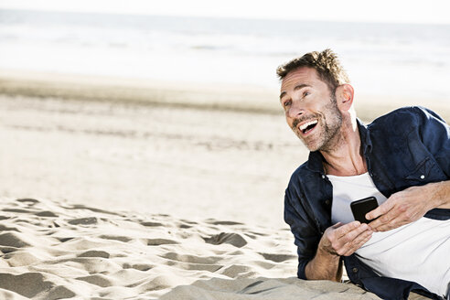 Happy man with cell phone on the beach - FMKF04205