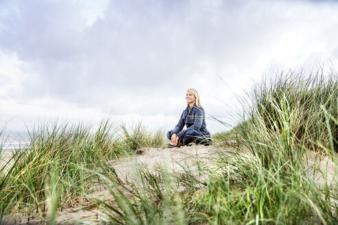 Smiling woman sitting in dunes - FMKF04211