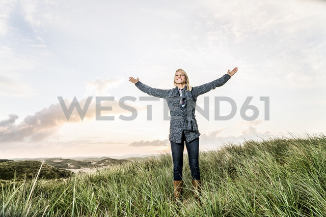 Happy woman standing in dunes with raised arms - FMKF04220 - Jo Kirchherr/Westend61