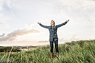 Happy woman standing in dunes with raised arms - FMKF04220
