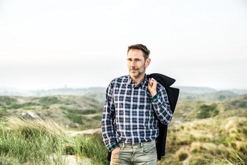 Portrait of man standing in dunes - FMKF04223