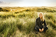 Portrait of smiling woman sitting in dunes - FMKF04229