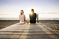 Couple with wine glasses sitting on boardwalk on the beach at sunset - FMKF04241
