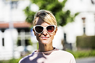Portrait of blond woman wearing sunglasses - FMKF04244