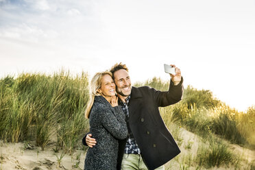 Happy couple in dunes taking a selfie - FMKF04247