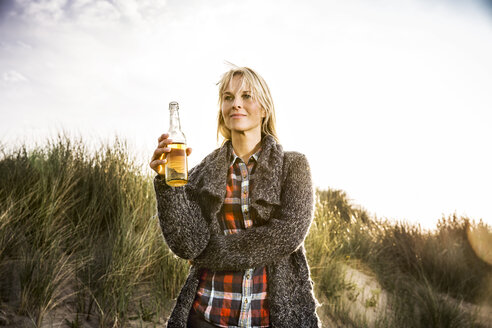 Smiling woman drinking a beer in dunes - FMKF04250