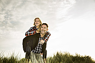 Happy playful couple in dunes - FMKF04253