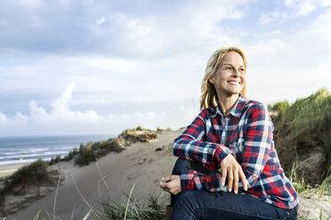 Smiling woman sitting in dunes - FMKF04256