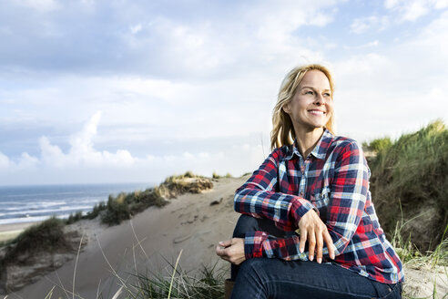 Smiling woman sitting in dunes - FMKF04256