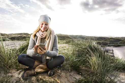 Smiling woman sitting in dunes using cell phones - FMKF04259